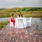 red-dress-table-couple-water-deck