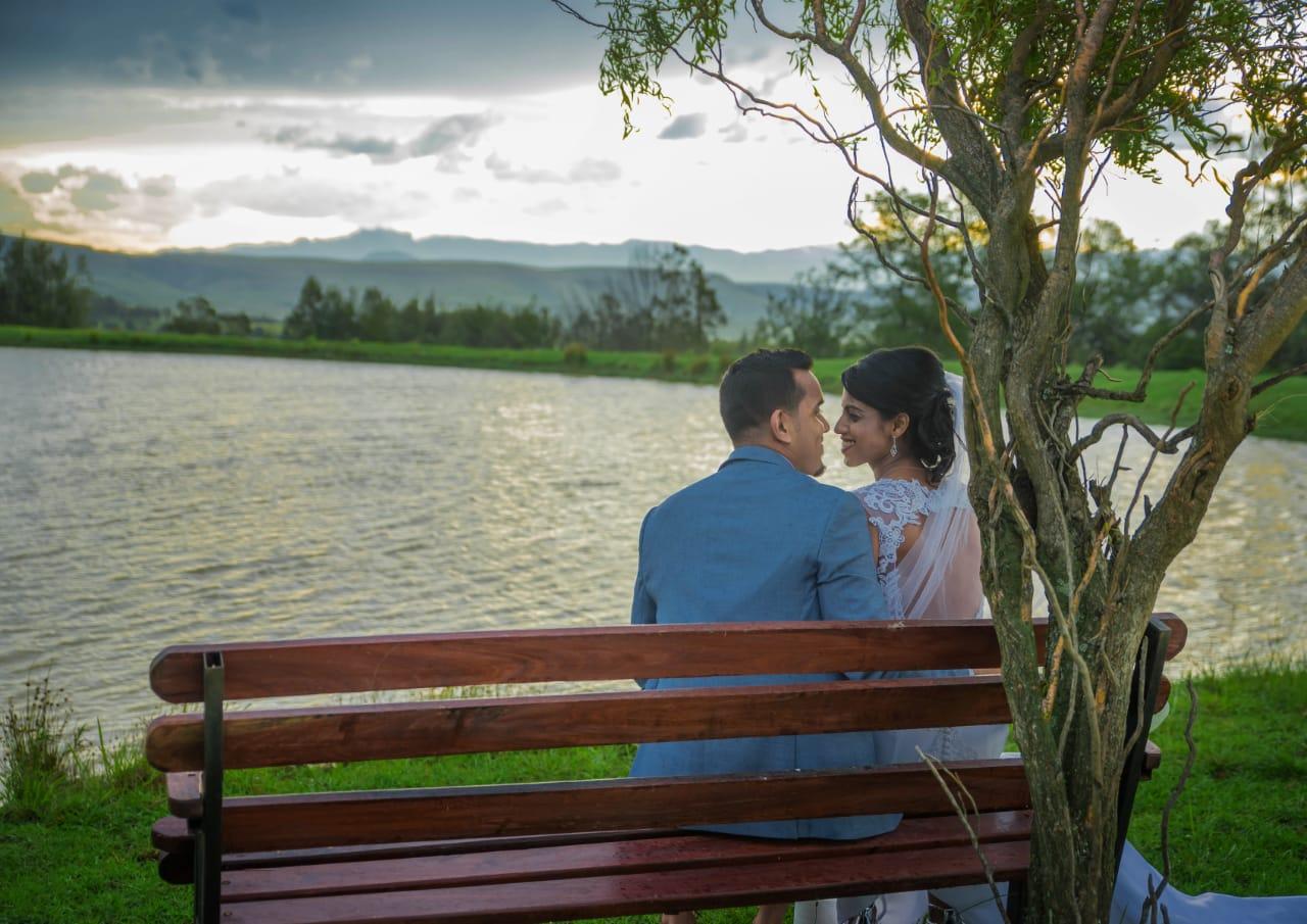 couple-smiling-lake-bench-trees